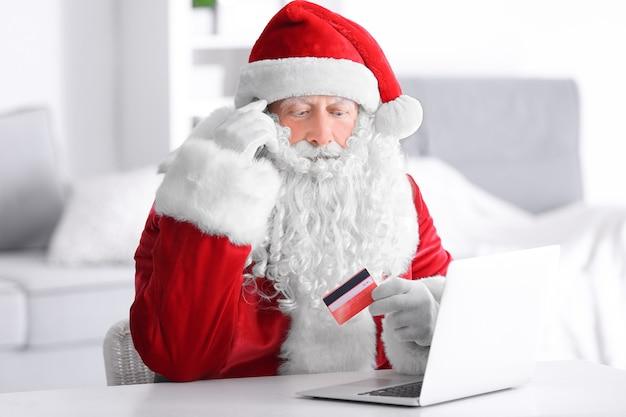 Święty mikołaj z laptopem i kartą kredytową w domu