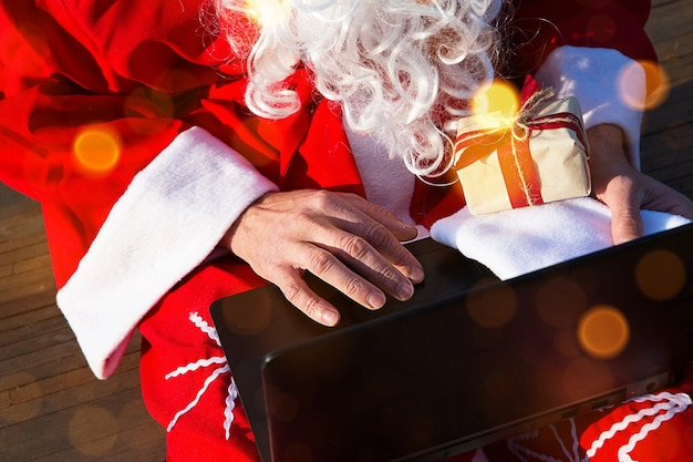 Święty mikołaj z laptopem i prezentem w ręku. zamów prezenty na boże narodzenie i nowy rok przez sklep internetowy. rezerwacja usług animatora na święta.
