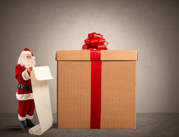 Święty mikołaj z listą prezentów i dużym pudełkiem na prezenty