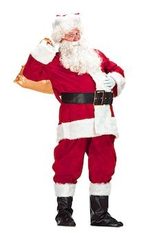 Święty mikołaj z luksusową białą brodą, czapką świętego mikołaja i czerwonym kostiumem na białym tle na białym tle z prezentami