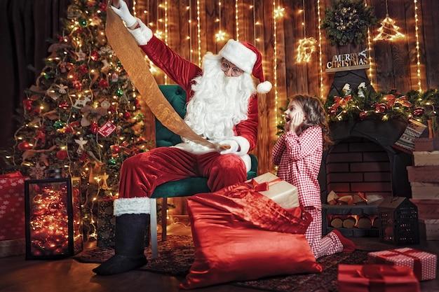 Święty mikołaj z małą śliczną zadziwiającą dziewczyną w piżamy pakuje prezenty