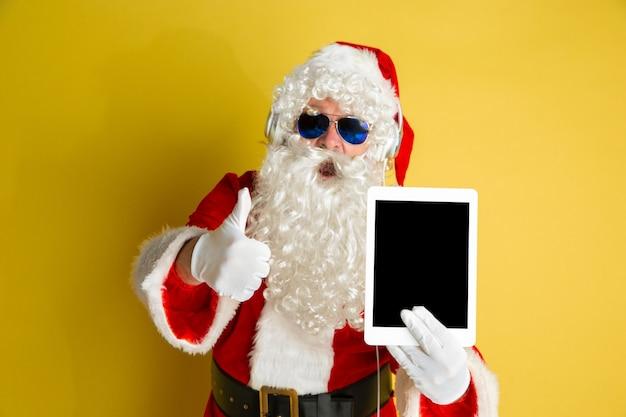 Święty mikołaj z nowoczesnymi okularami na żółtym tle studyjnym