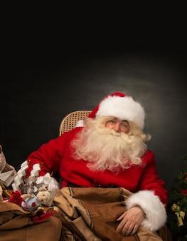 Święty mikołaj z ogromną torbą pełną świątecznych prezentów