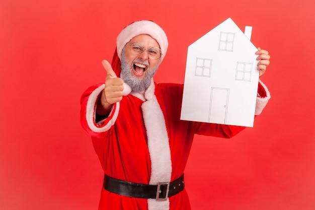 Święty mikołaj z papierowym domem w rękach pokazując kciuk do góry, polecam agencję nieruchomości.