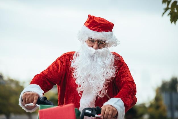 Święty mikołaj z prezentami w rowerze. czas świąt