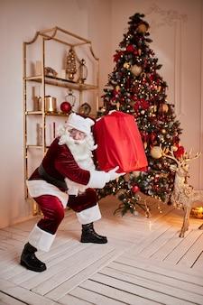 Święty mikołaj z wielką czerwoną torbą prezentów spieszy się, by przynieść prezenty dzieciom. nowy rok i wesołych świąt, koncepcja wesołych świąt