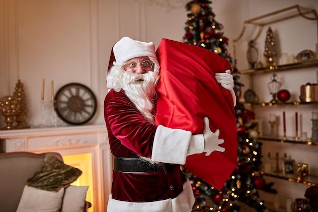 Święty mikołaj z wielką czerwoną torbą prezentów spieszy się, by przynieść prezenty dzieciom.