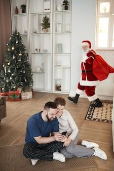 Święty mikołaj z wielkim workiem niesie prezenty bez podejrzeń, podczas gdy młoda para ogląda zdjęcia...
