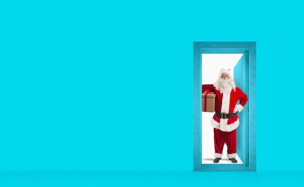 Święty mikołaj za drzwiami, aby dostarczyć prezent na koncepcję wysyłki w dzień bożego narodzenia
