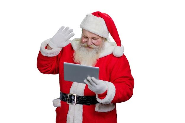 Święty mikołaj za pomocą tabletu komputerowego.