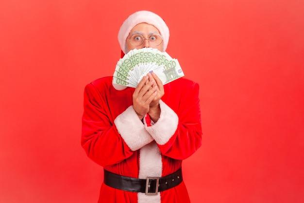 Święty mikołaj zakrywający pół twarzy wachlarzem banknotów euro, wielka bożonarodzeniowa wygrana na loterii.