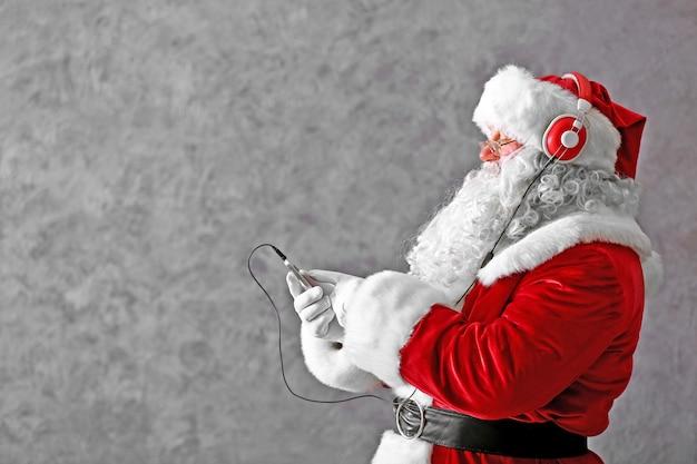 Święty mikołaj ze słuchawkami słucha muzyki na szarym tle ściany