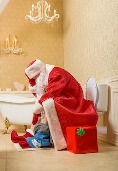 Święty mikołaj ze spuszczonymi spodniami siedzi na toalecie, pudełko w papier pakowy. świąteczny humor