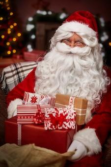 Święty mikołaj ze stosem prezentów świątecznych