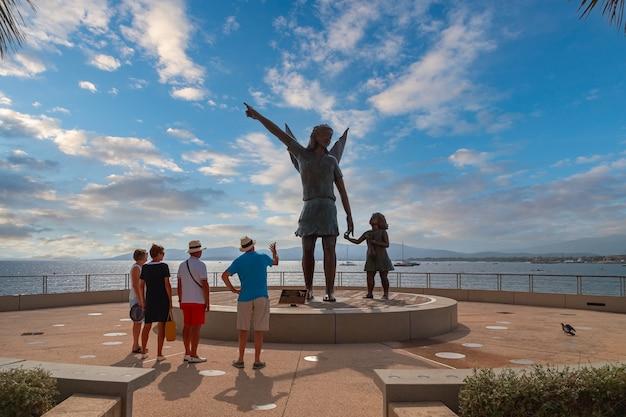 Święty raphael francja turyści podziwiający pomnik archanioła rafała i tobie w parku