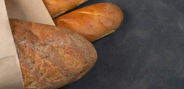 Świeża apetyczna bułka i bagietka z chrupiącą skórką na ciemnym tle w papierowej torbie. wolne miejsce po prawej, bagietka i chleb po lewej.