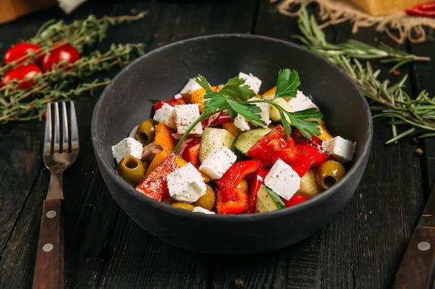Świeża apetyczna zdrowa grecka sałatka z warzywami i serem, boczny widok, horyzontalny