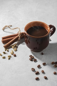 Świeża aromatyczna kawa w ceramicznej filiżance z przyprawami cynamonu i ziaren kardamonu na stole.