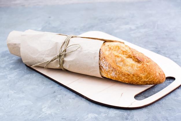 Świeża bagietka w papier do pakowania na deskę do krojenia na stole