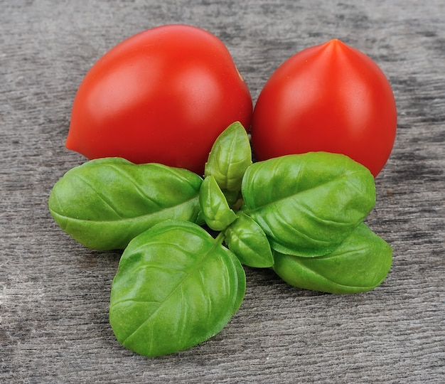 Świeża bazylia i pomidory na drewnianych stołach