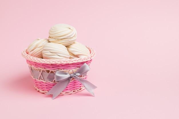 Świeża beza w wiklinowym koszu na różowo. pyszna słodycz jajek i cukru.