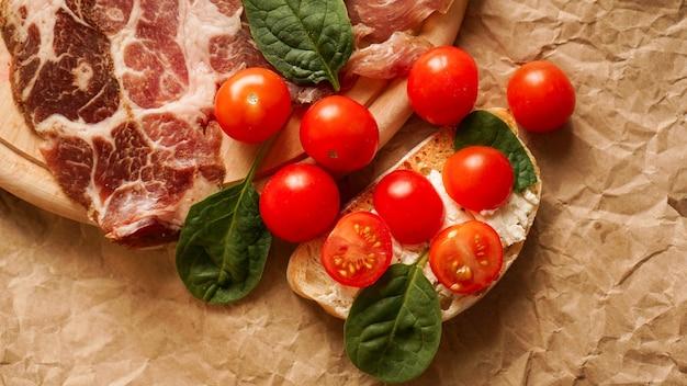 Świeża bruschetta na papierze rzemieślniczym. przystawka z ciabattą, serem, pomidorami, boczkiem i szpinakiem. pyszna przekąska