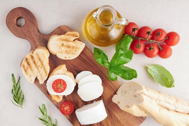Świeża bruschetta z pomidorami, mozzarellą i bazylią na desce do krojenia. tradycyjna włoska przekąska lub przekąska, antipasto. widok z góry. leżał na płasko. ciabatta z pomidorkami koktajlowymi.