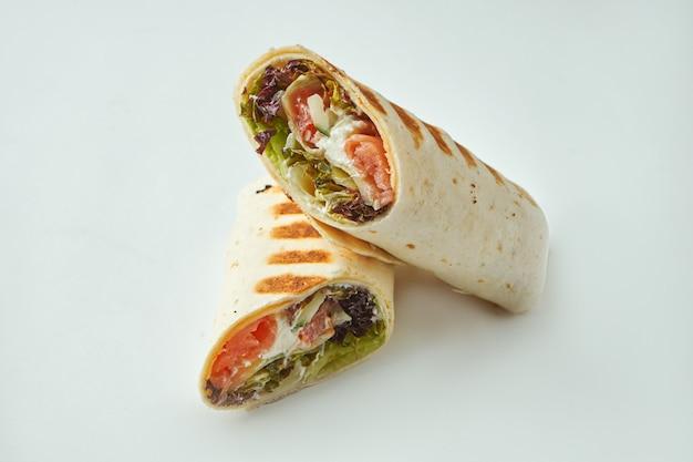 Świeża bułka z łososiem, twarogiem, ogórkiem i sałatą w chlebie pita na białym stole. shawarma z owocami morza