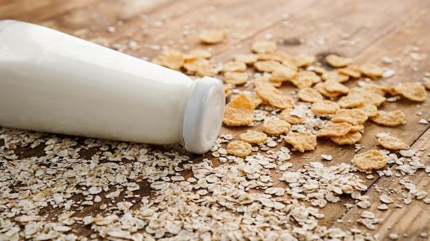 Świeża butelka mleka na powierzchni drewnianych z płatkami owsianymi i zbożami. koncepcja zdrowej i naturalnej żywności