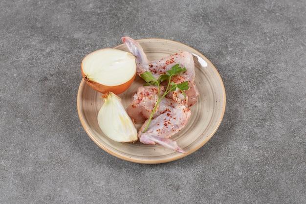 Świeża cebula z marynowanymi skrzydełkami kurczaka na talerzu