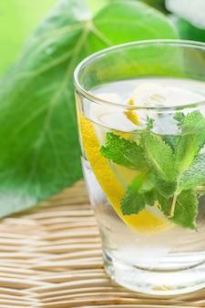 Świeża, chłodna woda z detoksykacji z plasterkami cytryny, mięta w mroźnym szkle na wiklinowym stole.