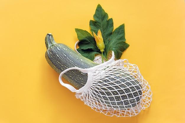 Świeża cukinia z zielonym liściem i kwiatkiem w ekologicznej siatkowej torbie na zakupy wielokrotnego użytku