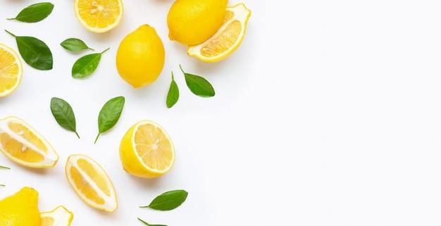 Świeża cytryna i plasterki z liśćmi odizolowywającymi na bielu.