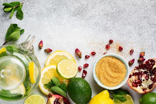 Świeża cytryna, limonka, granat, suszone kwiaty herbaty, herbata, cukier trzcinowy, liście mięty i szklany imbryk na szarym stole