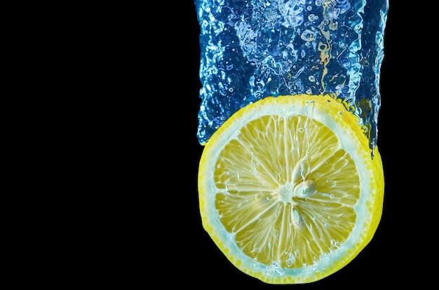 Świeża cytryna spada w wodzie z pluśnięciem na czarnym tle