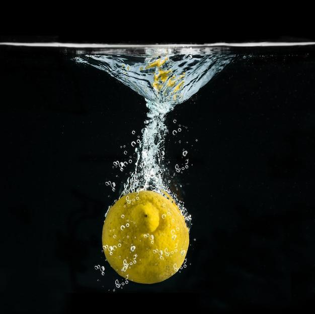 Świeża cytryna spada w wodzie