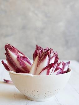 Świeża czerwona belgijska endywia na ociekaczu gotowym do przygotowania sałatki