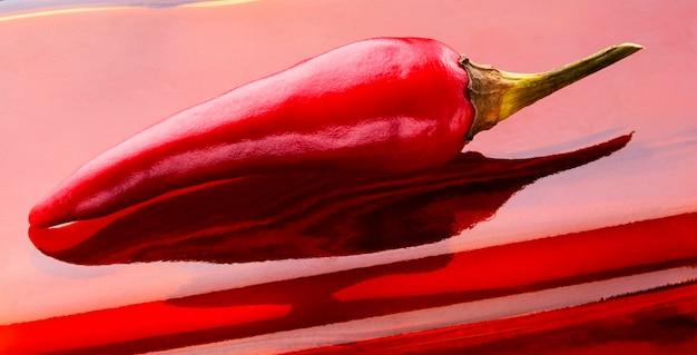 Świeża czerwona papryczka chili na czerwonym tle we włoszech to talizman na szczęście