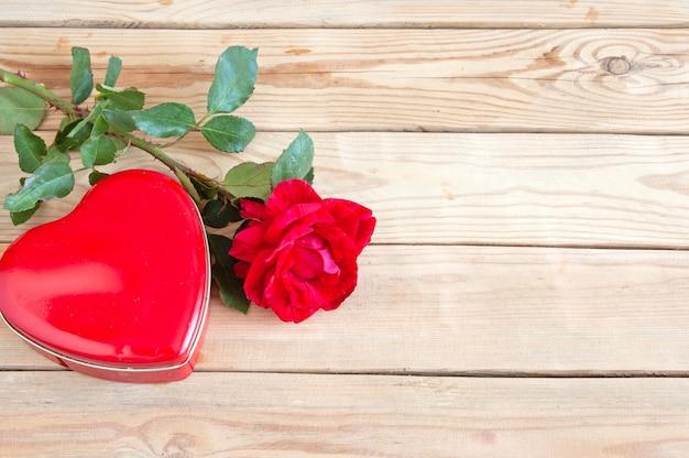 Świeża czerwona róża i serce pudełko na podłoże drewniane
