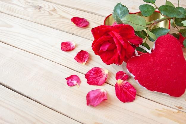 Świeża czerwona róża z płatkami i sercem na podłoże drewniane