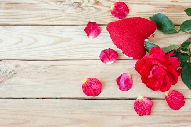 Świeża czerwona róża z płatkami i widokiem z góry serca w kształcie pudełka