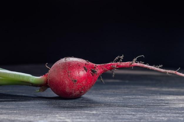 Świeża czerwona rzodkiew na przestrzeni czarnego drewna