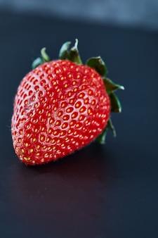 Świeża czerwona truskawka na ciemnej powierzchni. ścieśniać