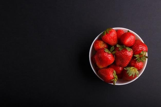 Świeża czerwona truskawka w białym pucharze na czerni. widok z góry.