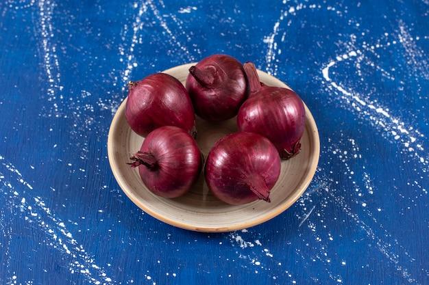 Świeża dojrzała czerwona cebula umieszczona na talerzu ceramicznym