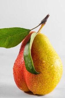 Świeża dojrzała gruszka z kroplami wody i liść na białym tle. smaczne owoce. orientacja pionowa