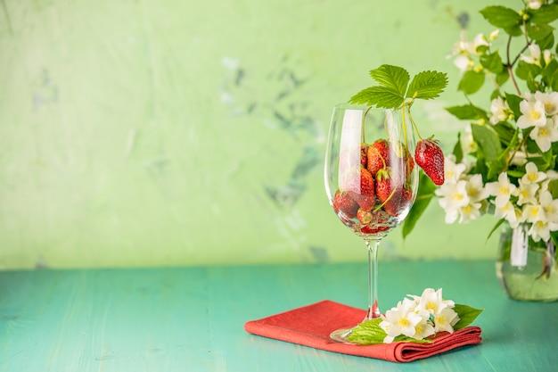 Świeża dojrzała surowa truskawka z zielonymi liśćmi w wina szkle na zieleni powierzchni.