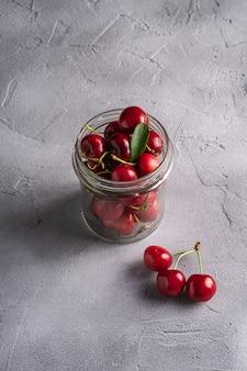 Świeża dojrzała wiśni gałąź blisko wiśni z zielonymi liśćmi w szklanym słoju