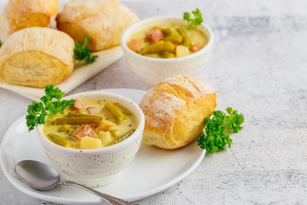 Świeża domowa kremowa zupa jarzynowa na białej misce z bułką i łyżką.
