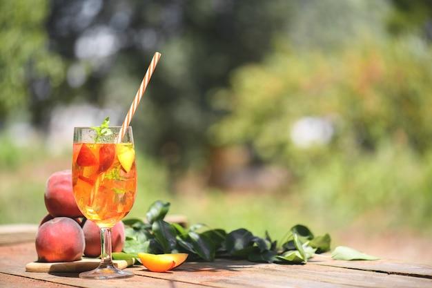 Świeża domowa słodka herbata brzoskwiniowa z plasterkami mięty i brzoskwini, letni zimny napój owocowy na świeżym powietrzu. kolorowy koktajl i bezalkoholowy na drewnianym stole